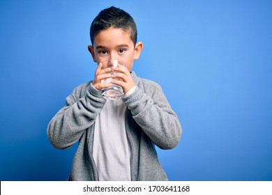Adorable toddler drinking glass of healthy water to refreshment standing over isolated blue background