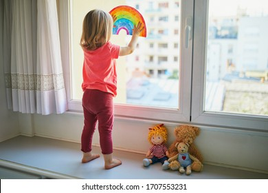 Adorable toddler girl attaching rainbow drawing to window glass as sign of hope. Creative games for kids staying at home during lockdown. Self isolation and coronavirus quarantine concept - Shutterstock ID 1707553231