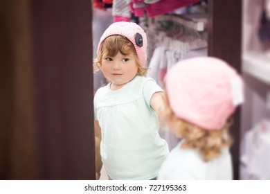 Adorable toddler girl in children apparel store looking at the mirror, choosing clothes, fitting warm autumn knitted hat, cute little shopper