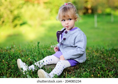 Adorable toddler girl with curly blond hair in knit purple dress and grey jacket playing outdoors on beauty sunny day