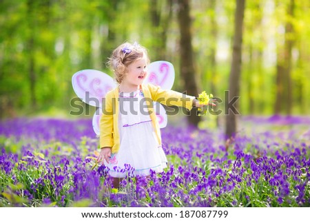 11734102f Adorable toddler girl with curly hair wearing a fairy costume with purple  wings and yellow dress