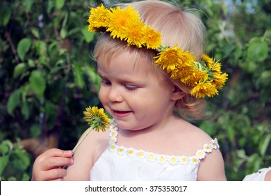 Adorable toddler girl with dandelion wreath on her head smelling the yellow flower