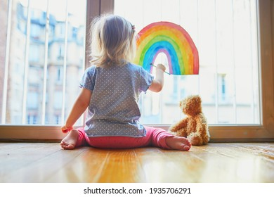 Adorable toddler girl drawing rainbow on window glass as sign of hope. Creative games for kids staying at home during lockdown. Self isolation and coronavirus quarantine concept