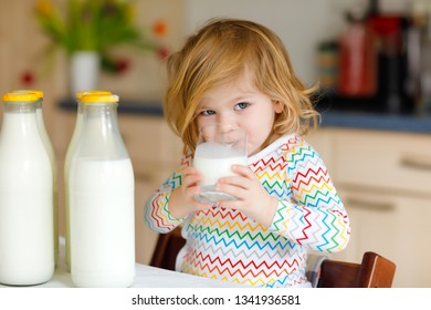 Adorable toddler girl drinking cow milk for breakfast. Cute baby daughter with lots of bottles. Healthy child having milk as health calcium source. Kid at home or nursery in the morning