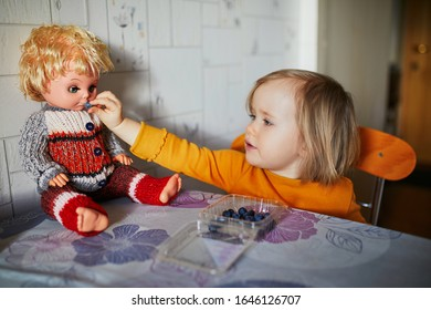 Adorable toddler girl eating blueberries and feeding her doll. Toddler role playing at home