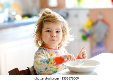Adorable toddler girl eating healthy porrige from spoon for breakfast. Cute happy baby child in colorful pajamas sitting in kitchen and learning using spoon.