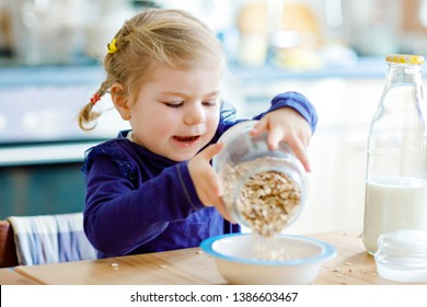 Adorable toddler girl eating healthy oatmeals with milk for breakfast. Cute happy baby child in colorful clothes sitting in kitchen and having fun with preparing oats, cereals. Indoors at home