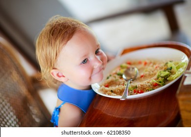 Adorable toddler girl eating healthy lunch