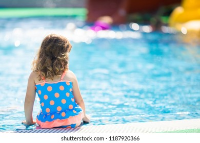 Adorable toddler girl having fun at the water park (aquapark)