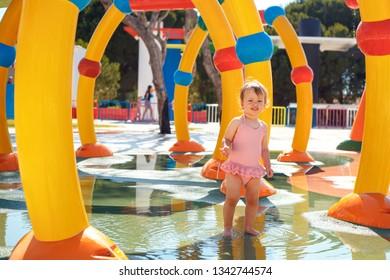 Adorable toddler girl having fun in aquapark. Enjoying day trip to an aqua amusement park during summer family vacation