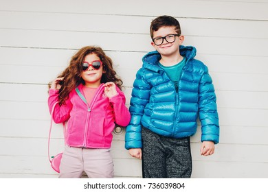 Adorable toddler girl and her big brother posing outdoors against white wooden background, wearing pink fleece jacket and blue padded coat