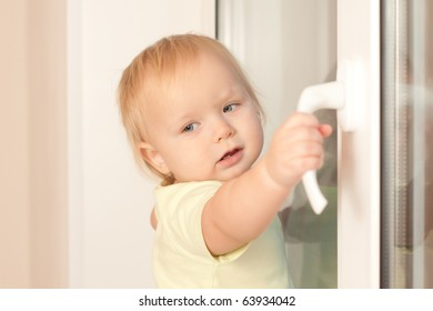 Adorable toddler girl holding window knob