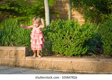 Adorable toddler girl jumping of fencing on a warm summer day