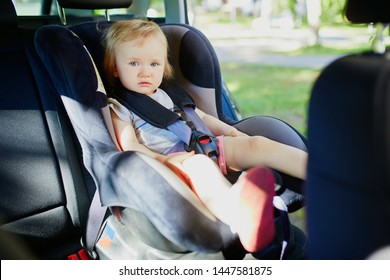 Adorable toddler girl in modern car seat. Little kid traveling by car. Child safety on the road. Trip with a baby.
