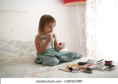 adorable toddler girl paints lips with her mother's lipstick, like mom. The concept of a happy childhood and role-playing game.
