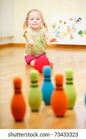 Adorable toddler girl playing bowling at home