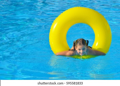 Adorable toddler girl playing with her inflatable tube, summer vacation concept