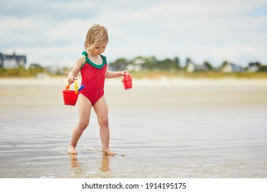 Adorable toddler girl playing on the sand beach at Atlantic coast of Brittany, France. Small child enjoying vacation by the sea or ocean. Travelling with kids