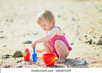 Adorable toddler girl playing with sand on the beach. Child spending vacation on the Atlantic coast in Normandy, France. Outdoor activities for kids
