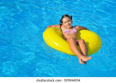 Adorable toddler girl relaxing in swimming pool, summer vacation concept