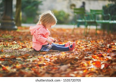 Adorable toddler girl sitting on the ground in Tuileries garden in Paris, France. Happy child enjoying warm and sunny fall day. Outdoor autumn activities for kids