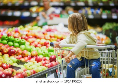 Adorable toddler girl sitting in the shopping cart in a food store or a supermarket. Little kid going shopping. Healthy food for kids
