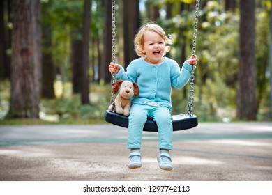Adorable toddler girl with soft toy dog having fun on a swing on summer day. Little girl playing at playground.