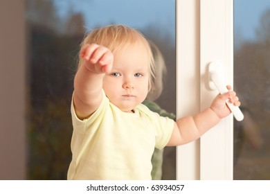 Adorable toddler girl stay on the window sill hold knob