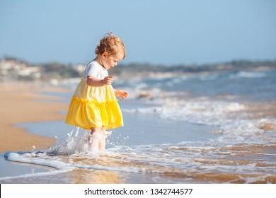 Adorable toddler girl wearing yellow dress splashing in ocean waves on beautiful summer day