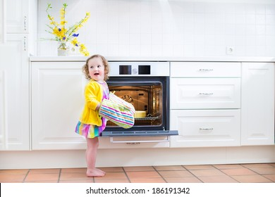 Adorable toddler girl in a yellow dress wearing colorful mittens playing in the kitchen next to a modern white oven helping by cooking and baking an apple pie in a home with white interior