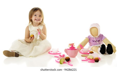 An adorable toddler happily having a party with her dolly.  On a white background.