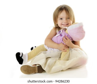 An adorable toddler happily hugging her baby doll.  On a white background.