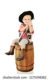 An adorable toddler playing cowboy. He sits on an old barrel looking up as he points his toy guy.  On a white background.