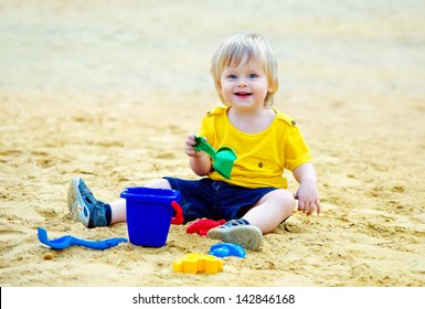 Adorable toddler playing with his toys in the sandpit