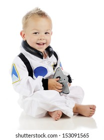 An adorable toddler playing with a toy shuttle while barefoot in his astronaut costume.  On a white background.
