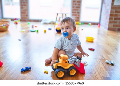 Adorable toddler sitting on the floor using pacifier playing around lots of toys at kindergarten
