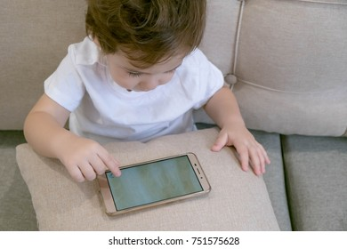 Adorable toddler sitting on the sofa in the living room and playing. Child learning how to use smartphone. Boy texting on the phone. - technology and lifestyle concept