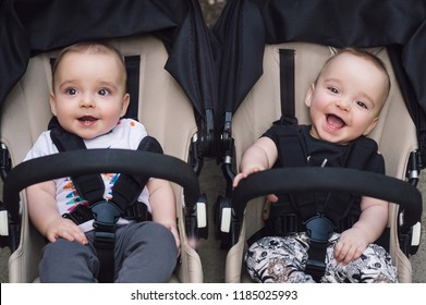 Adorable twin baby boys sitting in stroller and smiling happily. Childhood emotions. Nursing twins