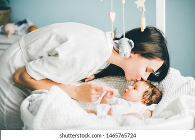 Adorable two month old baby girl lying on the bad. Mother holding daughter hand and kissing her. Mother standing near the cradle. Concept photo parenthood and motherhood.