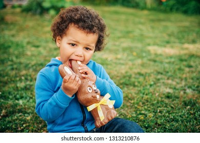 Adorable two year old african toddler boy eating chocolate bunny on backyard