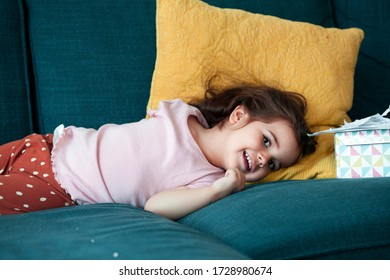Adorable two years old toddler baby girl lies on sofa in the living room,smiling and looking in to the camera.Relaxed and happy childhood concept