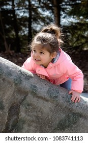 Adorable two-year-old little girl, Lebanese-Caucasian with brown hair and eyes, looks upward and to the left as she tries to climb higher up a large tree trunk. Hair in messy bun, wearing pink jacket.