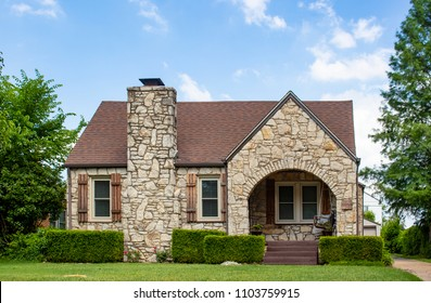 Adorable vintage rock home with rustic wood shutters and an arched porch with porch swing- curb appeal