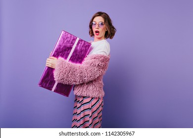 Adorable white young woman posing on purple background with sparkle gift box. Birthday girl with surprised face expression holding her present.