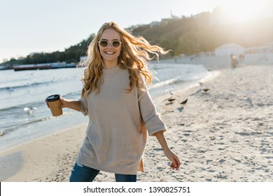 Adorable woman in casual sweater posing at sea. Stunning fair-haired girl enjoying autumn day near ocean