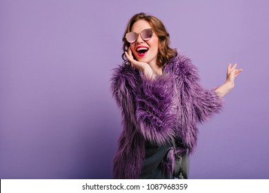 Adorable woman expressing true positive emotions during photoshoot in purple fur coat. Indoor portrait of active glamorous girl standing in cofident pose and smiling.