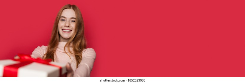 Adorable woman with freckles and red hair is smiling at camera receiving a present on a red studio wall with free space