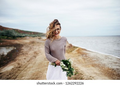 Adorable woman in glasses, sweater and white dress runs along the sea shore