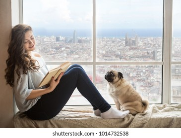 Adorable woman with her dog relaxing reading book next to the Barcelona view window