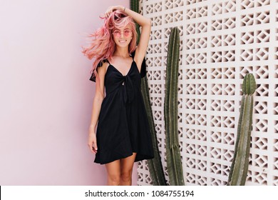 Adorable woman in stylish sunglasses expressing happiness during photoshoot near cactus. Cheerful girl with pink hair laughing while posing beside exotic plants on white background.